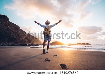 Young man arms outstretched by the sea at sunrise enjoying freedom and life, people travel wellbeing concept Royalty-Free Stock Photo #1510276562