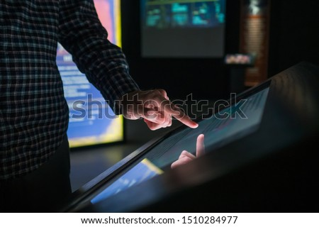 Man hand using interactive touchscreen display of electronic multimedia terminal at modern museum or exhibition. Evening time, low light illumination. Education, futuristic and technology concept #1510284977