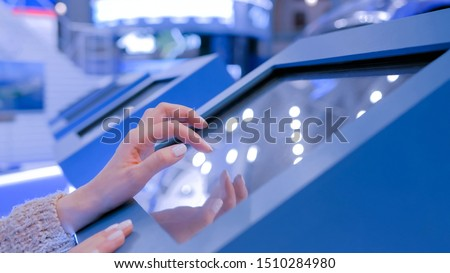 Woman hand using interactive touchscreen display of electronic multimedia terminal at modern technology exhibition. Education, futuristic and technological concept #1510284980