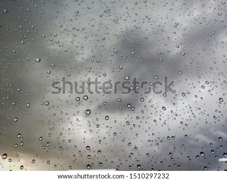 Rain water droplets with houses in background in City with dark clouds. Rain water droplets on Glass during Rain, dark clouds and detailed water droplets. Rain drops on window glasses surface Natural  #1510297232