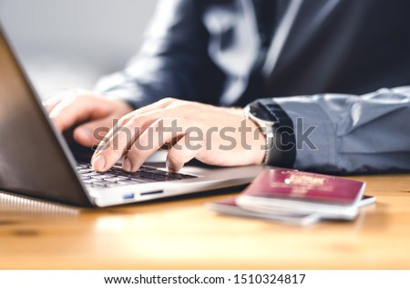 Man with passport and laptop. Travel document and identification. Immigrant writing electronic application for citizenship. Apply for digital visa. Online flight ticket or web check in. #1510324817