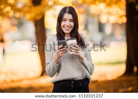 Beautiful woman using phone and drink coffee in autumn park. #1510331237