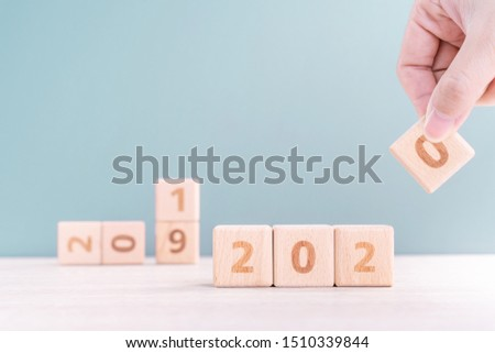 Abstract 2020 & 2019 New year countdown design concept - woman holding wood blocks cubes on wooden table and green background, close up, copy space. #1510339844