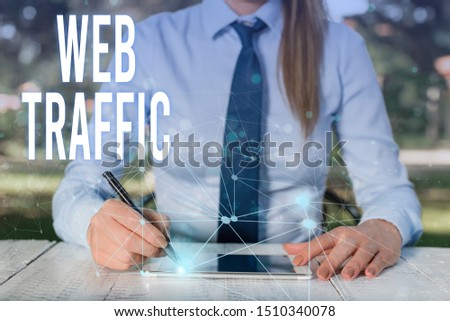 Conceptual hand writing showing Web Traffic. Business photo showcasing Amount of data sent and received by visitors to a website Female human wear formal work suit presenting smart device. #1510340078