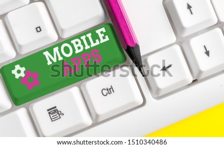 Conceptual hand writing showing Mobile Apps. Business photo showcasing small programs are made to work on phones like app store or app store White pc keyboard with note paper above the white #1510340486