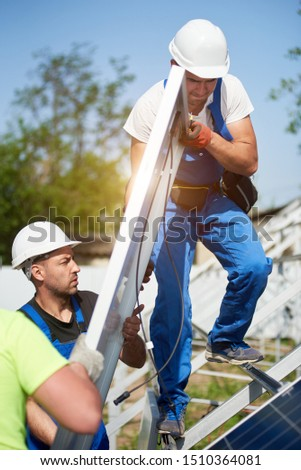 Three professional technicians adjusting heavy solar photo voltaic panel to metal platform on blue sky background. Stand-alone solar panel system installation, efficiency and professionalism concept. #1510364081