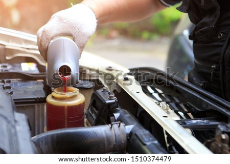 Male hand filling car power steering fluid Royalty-Free Stock Photo #1510374479