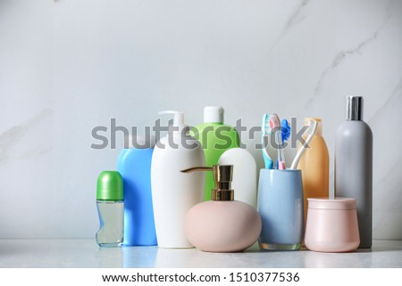 Roll-on deodorant and different toiletry on marble table near light wall Royalty-Free Stock Photo #1510377536