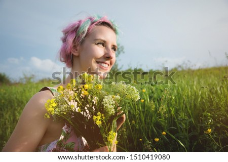 Portrait of a young happy smiling girl in a cotton dress with a bouquet of wildflowers #1510419080