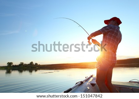 Young man fishing on a lake from the boat at sunset Royalty-Free Stock Photo #151047842