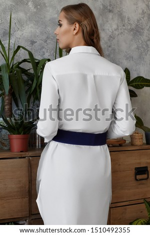 Medium full back shot of a young European lady dressed in a white long-sleeved tunic shirt and a wide blue elastic band. The fashion model with bronze hairgrips on her long wavy chestnut hair  #1510492355
