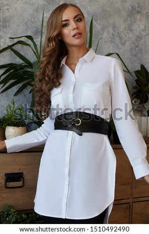 Medium full shot of a young European lady dressed in a black skirt, a white buttoned tunic shirt with pockets and a wide black leather belt with a bronze buckle and a thin leather strap tied #1510492490