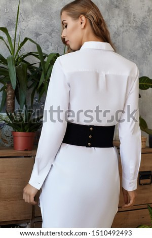 Medium full back shot of a young European lady dressed in a white long-sleeved tunic shirt and a wide black suede belt with tree golden press-studs. The fashion model bronze hairgrips  #1510492493