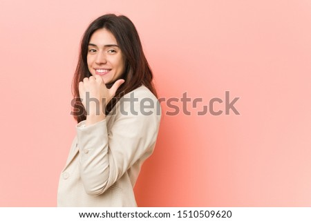 Young brunette business woman against a pink background points with thumb finger away, laughing and carefree. #1510509620