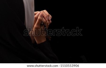 Top view of praying hands of Chatolic or Christian nun with praying rosary beads with cross in the hand. Black background and copy space. #1510553906