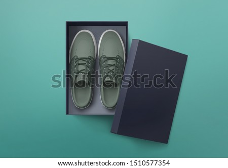Top view of plain shoe box mockup on green background. Green pair of shoes inside shoe box. #1510577354
