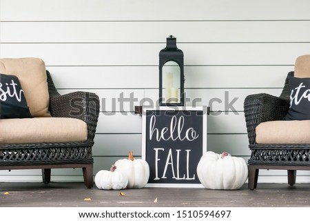 Stylish fall decorations in black and white on the front porch - hello fall