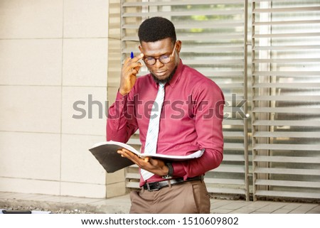 young businessman, african looking at his document holding a pen and know bezel wearing a red burgundy chemise #1510609802