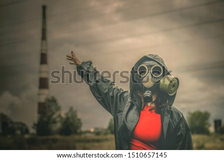 Woman in gas mask showing on a smoking chimney. #1510657145