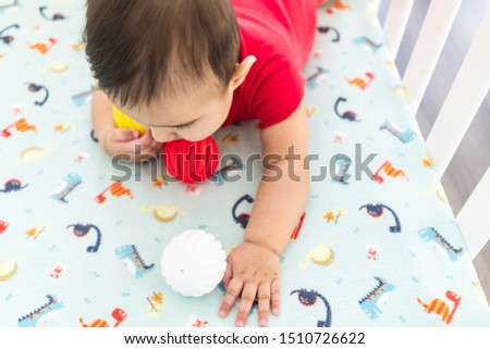 Baby playing with colorful toy rubber balls in the crib in a bright room. Child wearing a red bodysuit, laying on playful dinosaur crib sheet. #1510726622