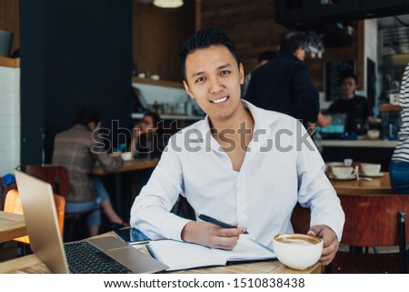 Confident modern smiling Asian man with cup of coffee sitting at table in cafe working with laptop and notepad looking at camera #1510838438