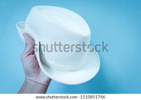 Hand holding a white hat in a blue background #1510851746