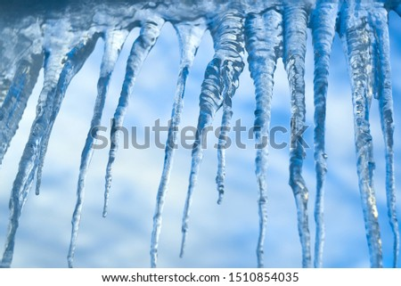 set of big icicles on sky background Royalty-Free Stock Photo #1510854035