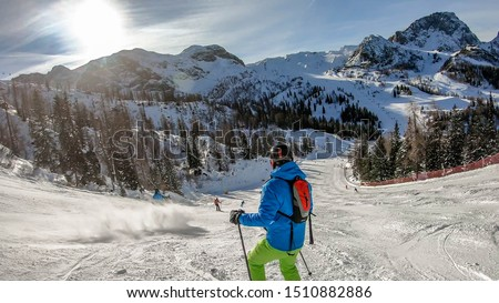 Morning in Alps, Nassfeld, Austria. Young skier stands on the graveled slope with his skies. Mountain slopes covered with snow. Sharp edges of the Alps. Pine trees covered with snow along the slopes. #1510882886