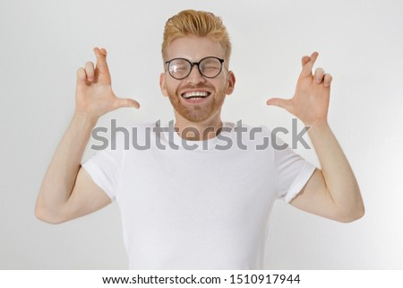 Fingers crossed, make a wish concept. Young redheaded guy with red beard cross finger for good luck. Hand sign, gesture for dreams come true. Happy smiling man in blank template white t shirt. Mockup