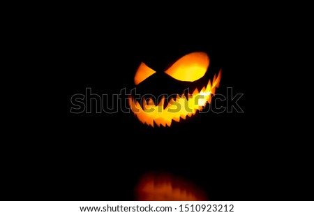 Halloween pumpkin smile and scary eyes for party night. Close up view of scary Halloween pumpkin with eyes glowing inside at black background. Selective focus #1510923212