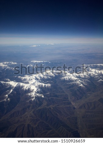 Landscape of a snowy mountains from a plane #1510926659