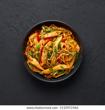 Chicken Schezwan Noodles or Hakka or Chow Mein in black bowl at dark background. Schezwan Noodles is indo-chinese cuisine hot dish with udon noodles, vegetables and chilli sauce or Schezwan sauce #1510951466