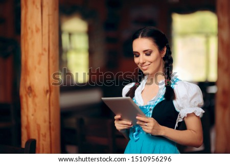 Oktoberfest Bavarian Waitress Holding PC Tablet Welcoming Guests. Restaurant hostess dressed in dirndl costume working in brewery  #1510956296