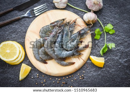 raw shrimps on wooden cutting board plate / fresh shrimp prawns for cooking with spices lemon on dark background in the seafood restaurant #1510965683