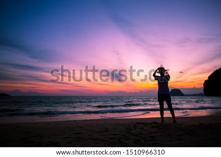 Silhouette of The girl is walking happily Use the phone at the beach during the sunset and her enjoying freedom feeling happy at sunset  #1510966310