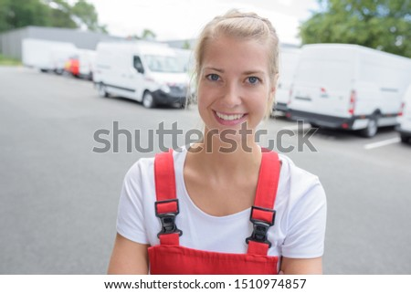 portrait of female delivery driver wearing red dungarees #1510974857