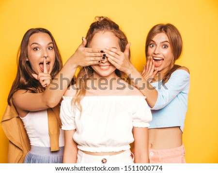 Three young beautiful smiling hipster girls in trendy summer clothes.Sexy carefree women posing near yellow wall in studio.Models surprising their friend.They cover her eyes and hugging from behind #1511000774