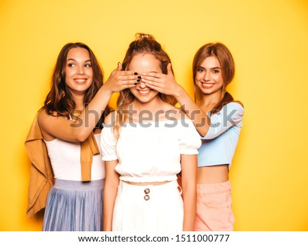 Three young beautiful smiling hipster girls in trendy summer clothes.Sexy carefree women posing near yellow wall in studio.Models surprising their friend.They cover her eyes and hugging from behind #1511000777