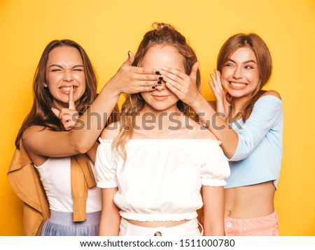 Three young beautiful smiling hipster girls in trendy summer clothes.Sexy carefree women posing near yellow wall in studio.Models surprising their friend.They cover her eyes and hugging from behind #1511000780