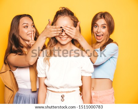Three young beautiful smiling hipster girls in trendy summer clothes.Sexy carefree women posing near yellow wall in studio.Models surprising their friend.They cover her eyes and hugging from behind #1511000783