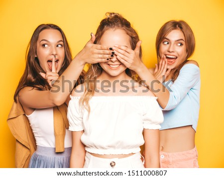 Three young beautiful smiling hipster girls in trendy summer clothes.Sexy carefree women posing near yellow wall in studio.Models surprising their friend.They cover her eyes and hugging from behind #1511000807