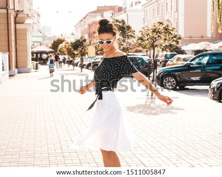 Beautiful smiling model dressed in elegant summer clothes.Sexy carefree girl dancing in the street background.Trendy modern businesswoman in sunglasses having fun in motion