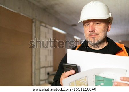 A man in a white helmet in a building under construction. The team leader checks the work of builders. Conformity assessment of construction documentation. Quality assurance. Builder. #1511110040