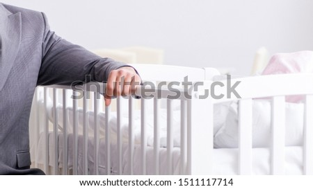 Young businessman trying to work from home caring after newborn #1511117714