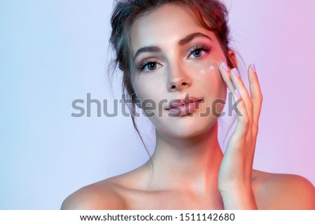 Cute woman with natural make-up applying moisturizing facial cream. Portrait of wonderful female looking at camera with calmness. Beauty and skincare concept #1511142680
