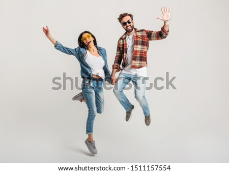 happy smiling couple isolated active jumping on white studio background, stylish man and woman in casual denim hipster outfit wearing shirt and sunglasses having fun together, dating friends #1511157554