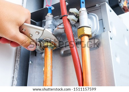 Plumber repairing a gas boiler of a heating home system in the boiler room. Close-up, selective focus. #1511157599
