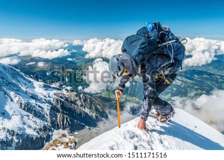 Extreme alpinist in high altitude on Aiguille de Bionnassay mountain summit, Mont Blanc massif, Chamonix, Alps, France, Europe #1511171516