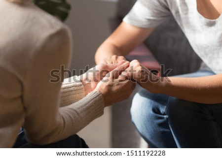 Close up of senior mom and adult daughter sit having sincere talk holding hands showing love and support, caring elderly mother and grownup offspring enjoy intimate close moment together at home #1511192228