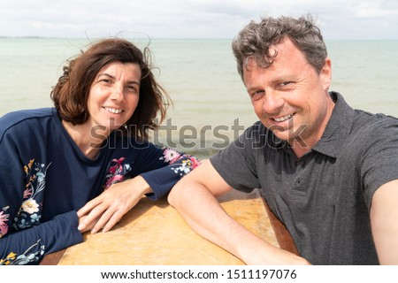 vacation couple sit on bar table on sea beach coast summer holidays make a selfie picture